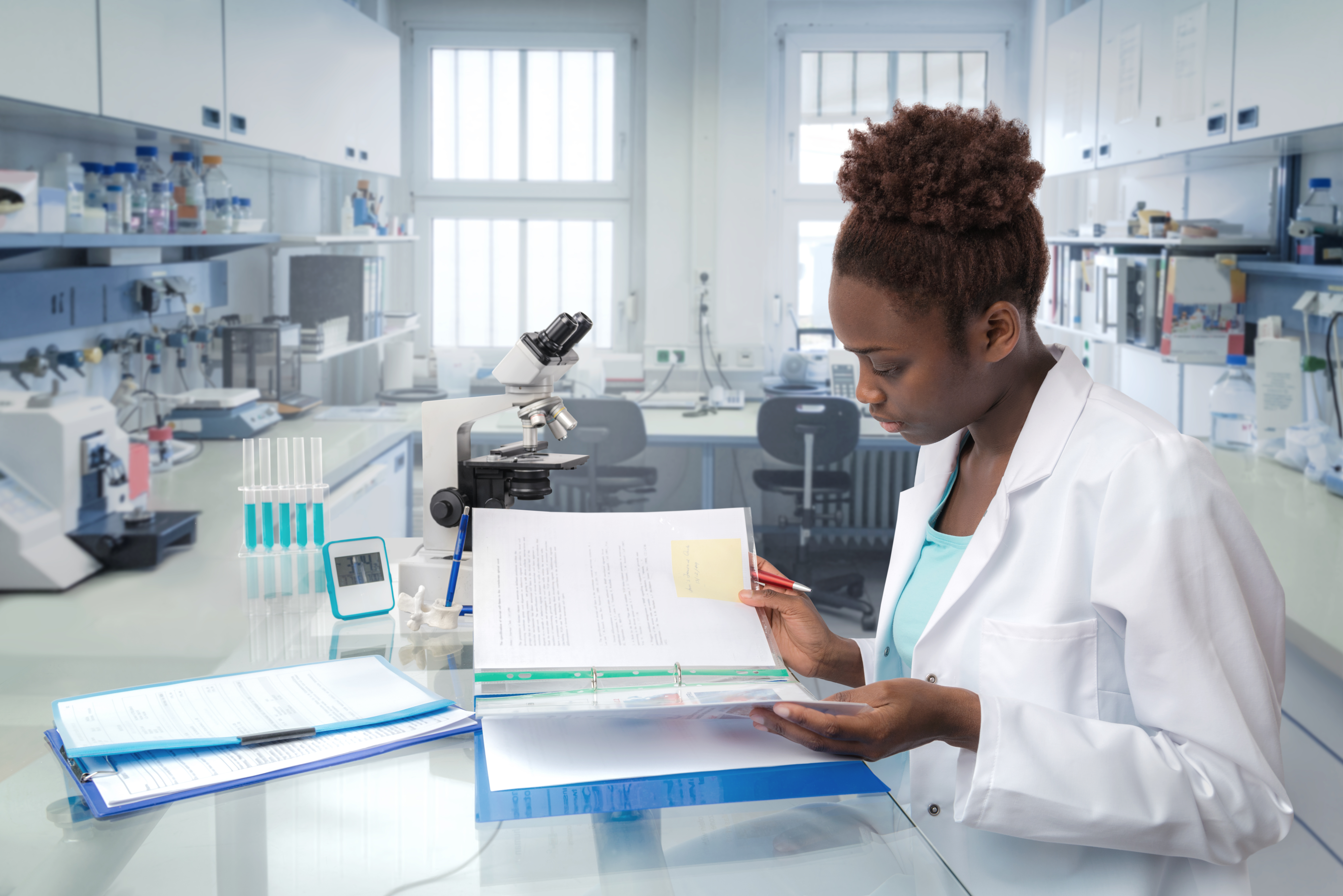 a woman scientist analyzing data in a binder at the lab