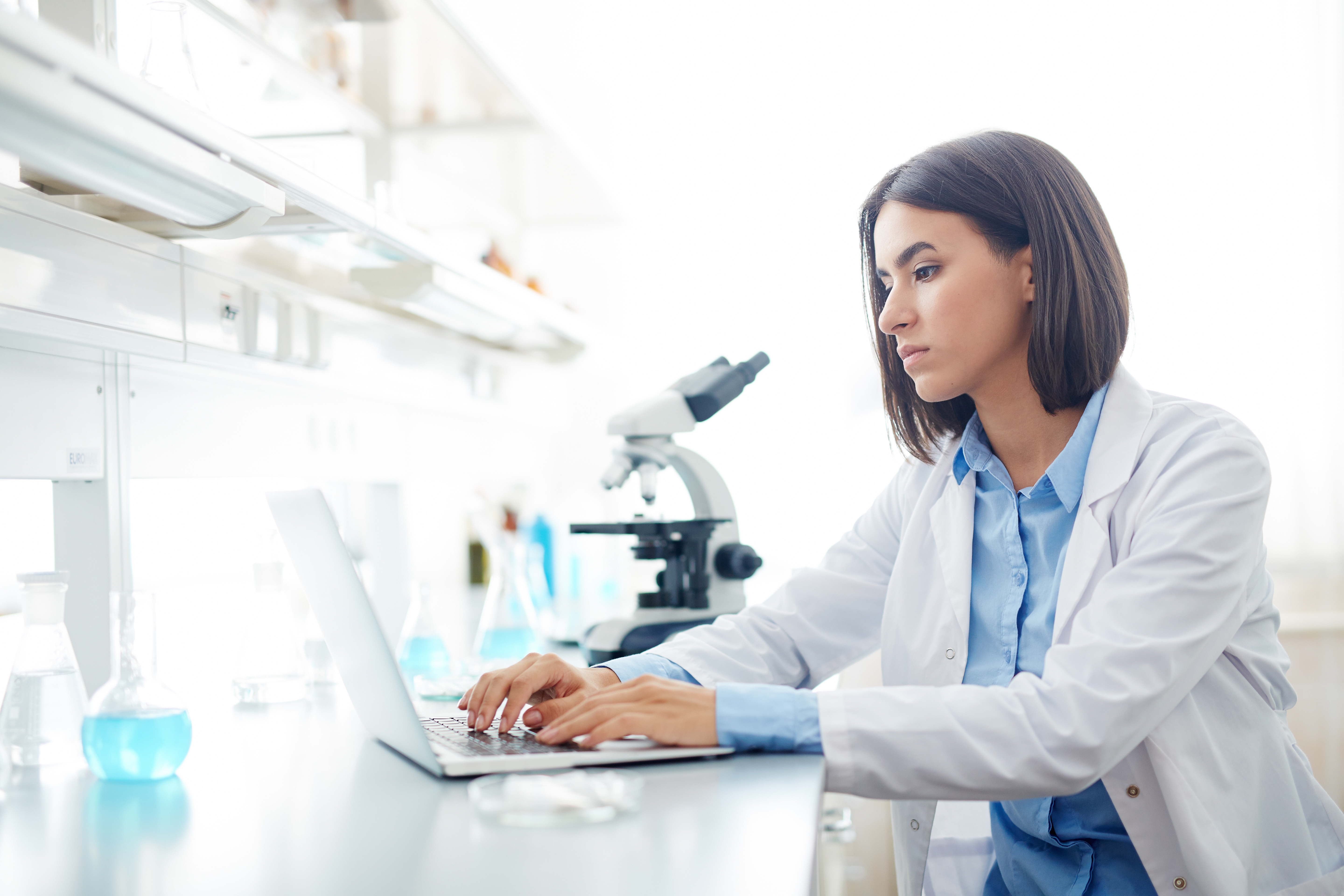 a woman scientist typing on laptop in a lab with a microscope next to her